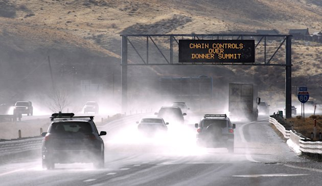 Traffic moves west along Interstate 80 west of Reno, Nev., as a heavy, wet storm hits Northern Nevada on Sunday, Dec. 2, 2012. A powerful storm delivered more snow and less rainfall Sunday to the Sierra than forecast, blunting the flooding danger on the Truckee River in California and Nevada, forecasters said. (AP Photo/Cathleen Allison)