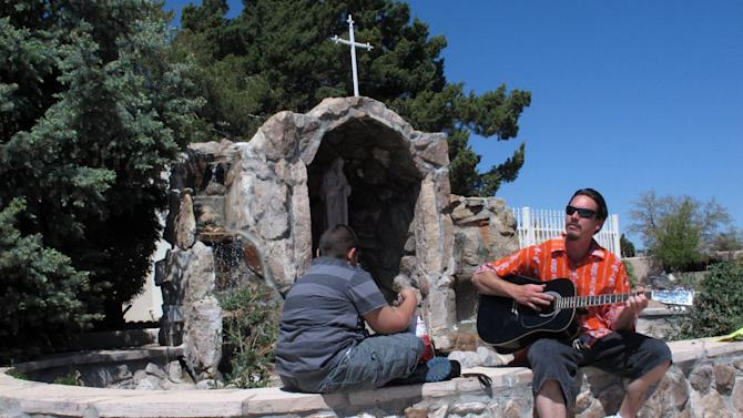 William Patterson, 34, of Pueblo, Colo., plays guitar outside the St. Jude Thaddeus Catholic Church in Albuquerque, Monday, April 29, 2013, a day after a man stabbed several churchgoers Sunday as Mass was ending. Police say four parishioners were injured, including church choir director Adam Alvarez, but none have life-threatening injuries. Lawrence Capener, 24, is charged with three counts with aggravated battery and is being held on $75,000 bail. (AP Photo/Russell Contreras)