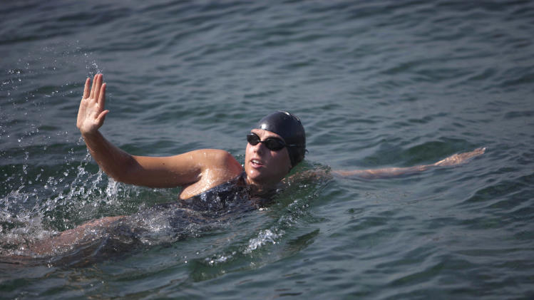 Australian swimmer Chloe McCardel waves to spectators as she begins her swim to Florida from the waters off Havana, Cuba, Wednesday, June 12, 2013. McCardel, 29, is bidding to become the first person to make the Straits of Florida crossing without the protection of a shark cage. American Diana Nyad and Australian Penny Palfrey have attempted the crossing four times between them since 2011, but each time threw in the towel part way through due to injury, jellyfish stings or strong currents. Australian Susie Maroney did it in 1997, but with a shark cage. (AP Photo/Ramon Espinosa)