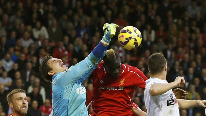 Hull City goalkeeper Eldin Jakupovic punches the ball as Liverpool's Mario Balotelli tries to score during their English Premier League soccer match at Anfield in Liverpool