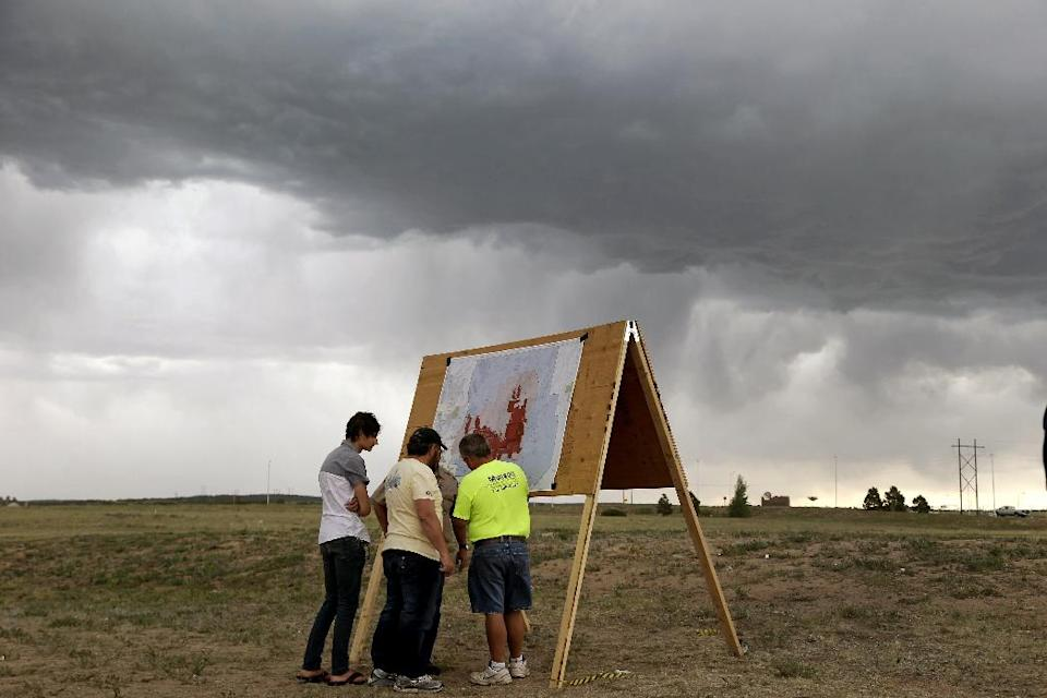 Residents look at a map detailing the progress of the Black Forest wildfire Sunday, June 16, 2013, in Colorado Springs, Colo. Fire crews were putting out hot spots Sunday to prevent flare ups in heavily wooded Black Forest, where hundreds of houses have been destroyed. (AP Photo/Marcio Jose Sanchez)