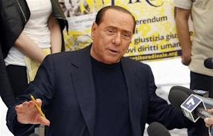 PDL leader Silvio Berlusconi talks with reporters as he signs a referendum on justice reforms and human rights in downtown Rome
