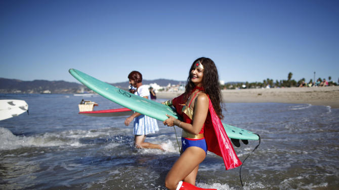 Denise Waling, 33, wades into the water dressed as Wonder Woman during the ZJ Boarding House Halloween surf contest in Santa Monica