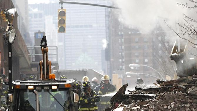 A firefighter applies water to rubble a day after a gas leak-triggered explosion, Thursday, March 13, 2014, in East Harlem, New York. Rescuers working amid gusty winds, cold temperatures and billowing smoke pulled additional bodies Thursday from the rubble of two apartment buildings that collapsed Wednesday. (AP Photo/Julio Cortez)