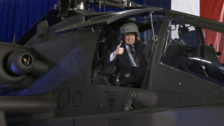 Ma poses for photographers from the cockpit of an AH-64E Apache attack helicopter at the Tainan military base