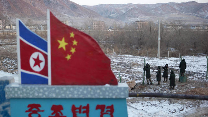 "FILE - In this Dec. 8, 2012 file photo, Chinese paramilitary policemen build a fence near a concrete marker depicting the North Korean and Chinese national flags with the words ""China North Korea Border"" at a crossing in the Chinese border town of Tumen in eastern China's Jilin province. China is trying to punish ally North Korea for its nuclear and missile tests, stepping up inspections of North Korean-bound cargo in a calibrated effort to send a message of Chinese pique without further provoking a testy Pyongyang government. (AP Photo/Ng Han Guan, File)"