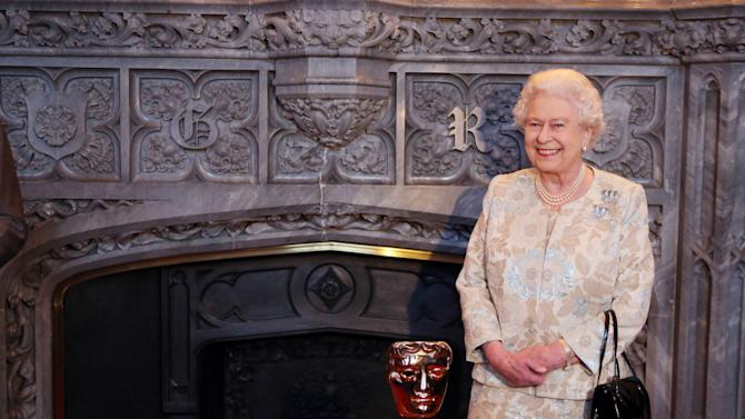 """Queen Elizabeth II receives an honorary British Academy award (Bafta) Thursday April 4 2013,  at Windsor Castle, west of London, from  actor and director Kenneth Branagh, unseen, in recognition of her lifetime's support of British film and television - and for being the most """"memorable Bond girl yet"""", in her London Olympics opening role. (AP Photo/Steve Parsons, pool)"""