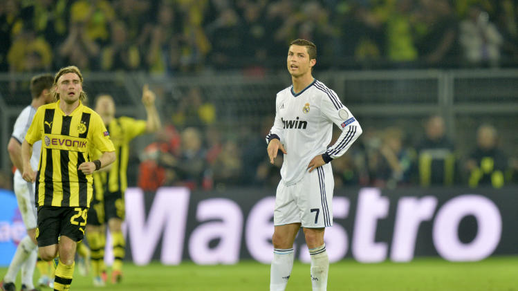 Madrid's Cristiano Ronaldo from Portugal reacts after Dortmund's Robert Lewandowski of Poland, background, celebrates scoring his side's 4th goal during the Champions League semifinal first leg soccer match between Borussia Dortmund and Real Madrid in Dortmund, Germany, Wednesday, April 24, 2013. (AP Photo/Martin Meissner)