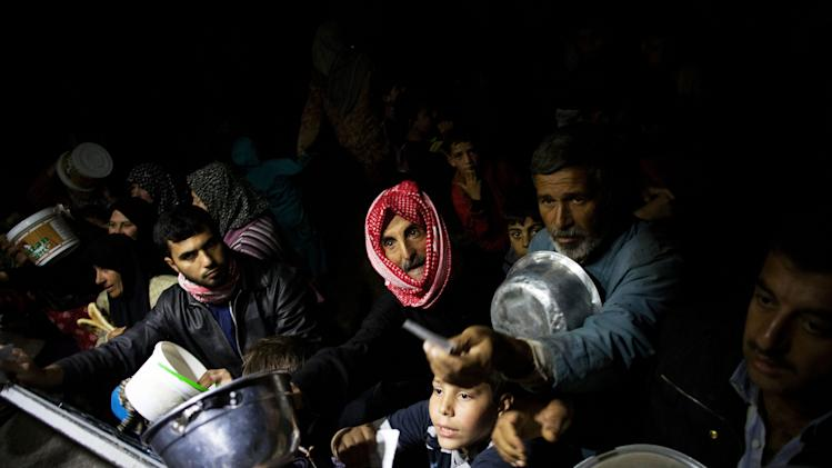 Displaced Syrian men wait for food near an NGO charitable kitchen in a refugee camp near Azaz, Syria, Tuesday, Oct. 23, 2012. (AP Photo/ Manu Brabo)