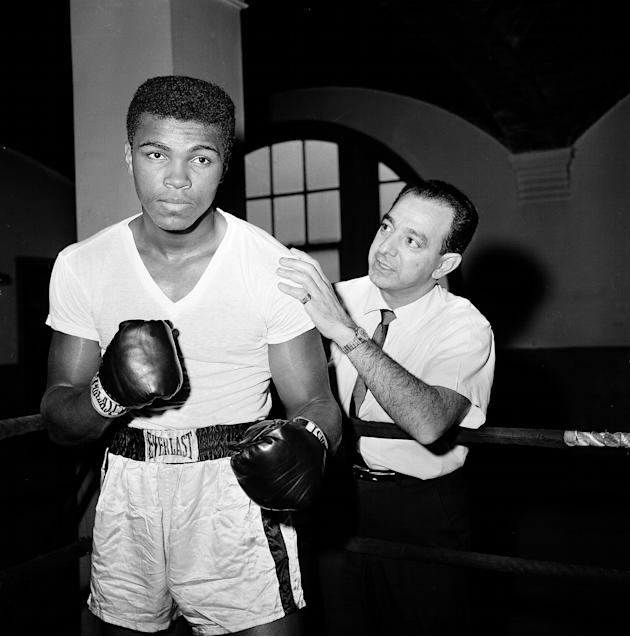 FILE - In this Feb. 8, 1962 file photo, a young Muhammad Ali  is seen with his trainer Angelo Dundee at City Parks Gym in New York. The three-time heavyweight boxing champion will celebrate a mileston