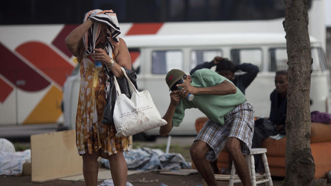 """In this photo taken Nov. 29, 2012, a woman, left, and a man smoke crack in Rio de Janeiro, Brazil. The South American country began experiencing a public health emergency in recent years as demand for crack boomed and open-air """"cracolandias,"""" or crack lands, popped up in the sprawling urban centers of Rio and Sao Paulo, with hundreds of users gathering to smoke the drug. The federal government announced in early 2012 that more than $2 billion would be spent to fight the epidemic, with the money spent to train local health care workers, purchase thousands of hospital and shelter beds for emergency treatment, and create transitional centers for recovering users. (AP Photo/Felipe Dana)"""