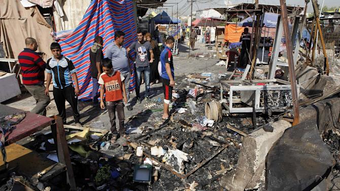 People inspect the aftermath of a car bomb attack on a store in the New Baghdad neighborhood of Baghdad, Iraq, Sunday, Aug. 11, 2013. A wave of car bombings targeting those celebrating the end of Ramadan across Iraq killed scores of people Saturday, a bloody reminder of the inability of Iraqi authorities to stop violence threatening to spiral out of control. (AP Photo/Hadi Mizban)