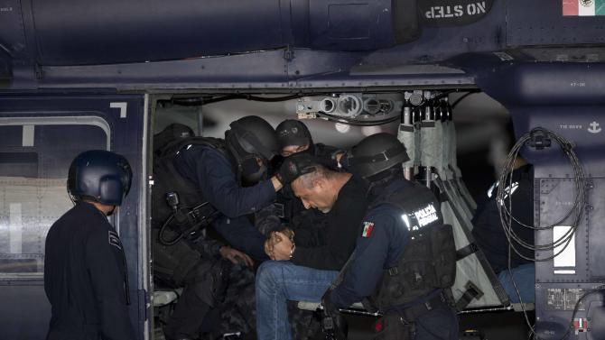 "Federal police escort who they identify as Servando ""La Tuta"" Gomez,"" leader of the Knights Templar cartel, during a news conference at the hangar of the Attorney General's Office in Mexico City, Friday, Feb. 27, 2015. Gomez, a former school teacher who became one of Mexico's most-wanted drug lords as head of the Knights Templar cartel, was captured early Friday by federal police, according to Mexican officials.  (AP Photo/Eduardo Verdugo)"