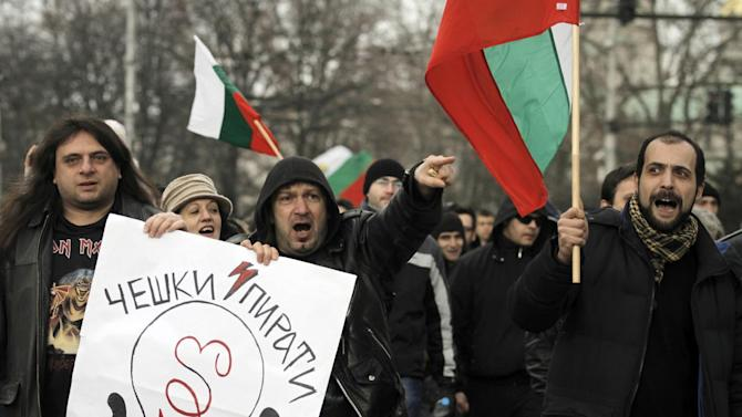 """Bulgarians shout slogans and carry poster reading """"CEZ - Czech pirates"""" as they protest against higher electricity and heating bills, in Sofia,  Sunday, Feb. 17, 2013. Thousands of angry Bulgarians chanted """"mafia"""" and """"resignation""""  demanded the expulsion of the three foreign-controlled power distributors that control the local market: Czech Republic's CEZ and Energo-Pro, and Austria's EVN   (AP Photo/Valentina Petrova)"""