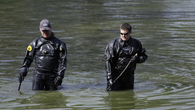 Divers search Meyers Lake for missing children Lyric Cook-Morrissey, 10, and Elizabeth Collins, 8, who disappeared last week, Friday, July 20, 2012, in Evansdale, Iowa. The girls' bikes were found last Friday afternoon near a bike trail at the edge of the lake. (AP Photo/Charlie Neibergall)