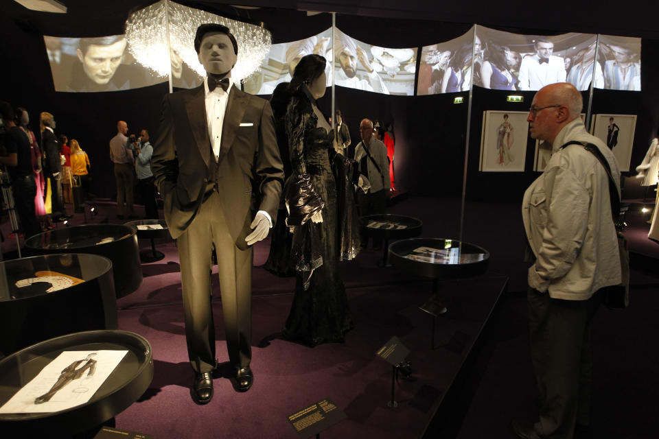 A visitor looks at a tuxedo worn by James Bond actor, Pierce Brosnan, in the film 'GoldenEye' on display in the exhibition 'Designing 007 - Fifty Years of Bond Style' at the Barbican centre in London, Thursday, July 5, 2012. (AP Photo/Sang Tan)