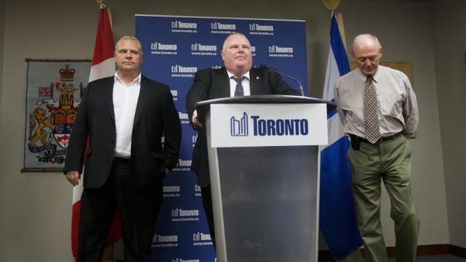 Toronto Mayor Rob Ford, center, denies allegations that he smokes crack cocaine and thanks his brother Toronto City Councillor Doug Ford, left, and Deputy Mayor Doug Holyday, right, as he speaks to the media at City Hall on Friday, May 24, 2013 in Toronto. Ford denies that he smokes crack cocaine and says he is not an addict after a video purported to show him using the drug. Ford did not say whether he has ever used the drug.   (AP Photo/The Canadian Press, Michelle Siu)