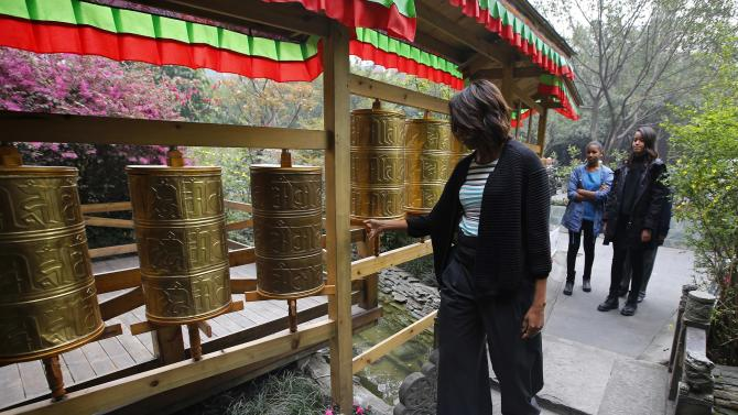 U.S. first lady Michelle Obama touches Tibetan prayer wheels outside a Tibetan restaurant in Chengdu