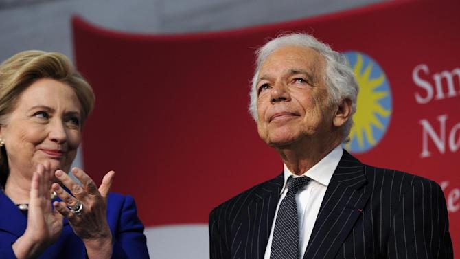 """Former Secretary of State Hillary Rodham Clinton applauds designer Ralph Lauren after Lauren received the James Smithson Bicentennial Medal """"for his embodiment of the American experience through the medium of fashion, design and philanthropy"""" Tuesday, June 17, 2014, during a ceremony at the Smithsonian's National Museum of American History in Washington. Lauren was honored his efforts to fund the conservation of the flag that inspired the national anthem. (AP Photo/Susan Walsh)"""
