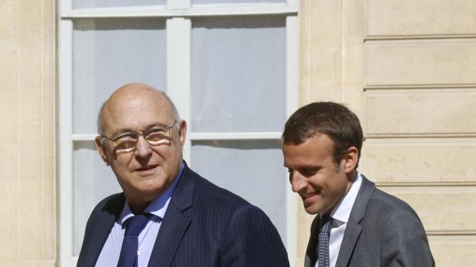 French Economy Minister Emmanuel Macron and Finance Minister Michel Sapin arrive to attend a meeting to apply the European Commission's plan to boost growth at the Elysee Palace in Paris
