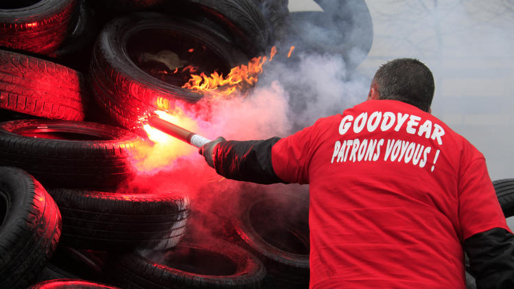"Goodyear employee burns tires, outside the Goodyear tyre company, in Amiens, northern France, Tuesday Feb. 26, 2013.   Workers at a dying French tire factory who've become the butt of American jokes are staging a day of last-ditch protests to try to save their jobs. The protests in the northern city of Amiens come after efforts to find a new buyer for the struggling plant have fizzled. An American executive who considered buying it sent a letter last week to the French government saying that France's economic model is too worker-friendly and discourages investment.  The  words on the shirt translates to  ""Bosses from Hell "".(AP Photo/Michel Spingler)(AP Photo/Michel Spingler)"