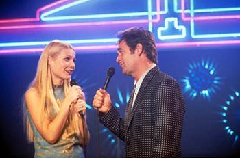 Gwyneth Paltrow (left) stars as an innocent Vegas showgirl who discovers a remarkable connection to a seasoned karaoke hustler ( Huey Lewis , right) in the funny, raucous world of the karaoke bars and chain hotels that link the interstates of Middle America, in Hollywood Pictures' Duets