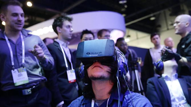 FILE - In this Jan. 7, 2014 file photo, show attendees play a video game wearing Oculus Rift virtual reality headsets at the Intel booth at the International Consumer Electronics Show(CES), in Las Vegas. Facebook said Tuesday, March 25, 2014, it has agreed to buy Oculus for $2 billion, betting that its virtual reality may be a new way for people to communicate, learn or be entertained. (AP Photo/Jae C. Hong, File)