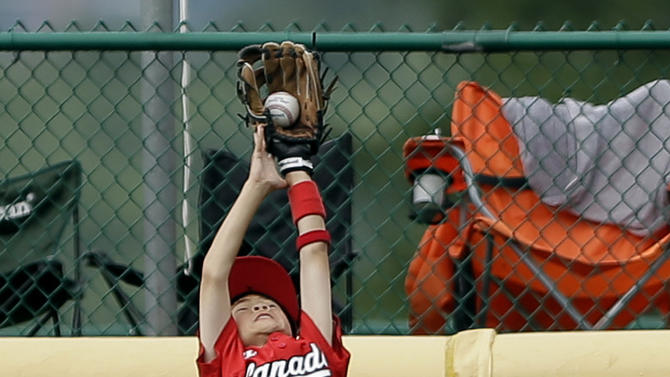 Vancouver, British Columbia's Carter Kada-Wong leaps to catch a two-run sacrifice fly by Willemstad, Curacao's Christopher Koeiman in the fifth inning of a pool play baseball game at the Little League World Series, Monday, Aug. 20, 2012, in South Williamsport, Pa. Curacao won 4-3. (AP Photo/Matt Slocum)