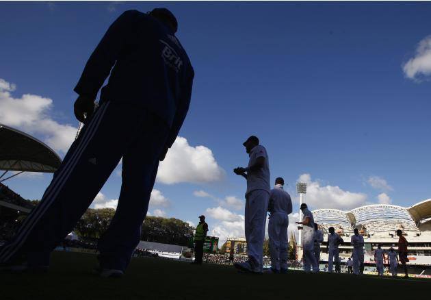 A security guard watches as England's captain Cook leads his team off the ground at the end of the first day's play in the second Ashes cricket test against Australia at the Adelaide Oval
