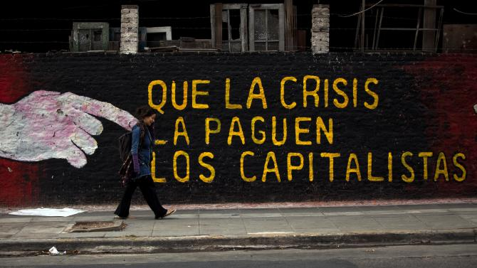 "In this photo taken Friday, May 18, 2012, a woman walks past a mural that reads in Spanish: ""Let the capitalists pay for the crisis,"" in Buenos Aires, Argentina. Some analysts believe Argentina is headed toward an economic slowdown and that inflation will continue to rise. The slowing has forced Argentine President Christina Fernandez's administration to alter the government's populist economic model, cutting some state subsidies. (AP Photo/Natacha Pisarenko)"