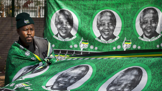 "A street vendor selling banners from the African National Congress (ANC) featuring images of Nelson Mandela stands by his wares outside the Mediclinic Heart Hospital where former South African President Nelson Mandela is being treated in Pretoria, South Africa Saturday, June 29, 2013. The White House issued a statement Saturday that US President Barack Obama plans to visit privately with relatives of former South African President Nelson Mandela, during his visit to South Africa, but doesn't intend to see the critically ill anti-apartheid activist he has called a ""personal hero."" (AP Photo/Ben Curtis)"