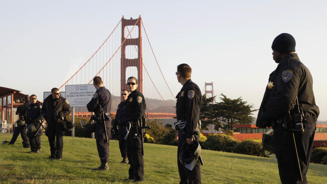 California Highway Patrol members stand watch at the Golden Gate Bridge in preparation for possible May Day protests in San Francisco, Tuesday, April 1, 2012.  Protesters had backed away from a call to block the bridge. But scores of California Highway Patrol officers nonetheless lined the span and gathered around the toll plaza this morning. (AP Photo/Eric Risberg)