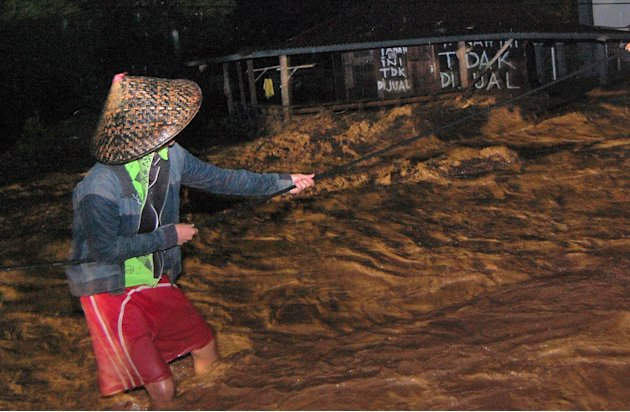 PADANG, 24/7 - BANJIR BANDANG PADANG. Seorang warga berpegangan pada sebuah tali melintasi banjir di Kelurahan Limaumanis, Kecamatan Pauh, Padang, Sumbar, Selasa (24/7) malam. Banjir bandang di sekita