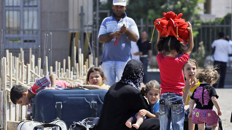 Syrian refugees arrive at the Turkish Cilvegozu gate border, Monday, Sept. 2, 2013. Routine prevailed at a US-Turkish airbase in southern Turkey on Monday, a day after the US alleged that sarin gas was used in an August chemical weapons attack in Syria. (AP Photo/Gregorio Borgia)