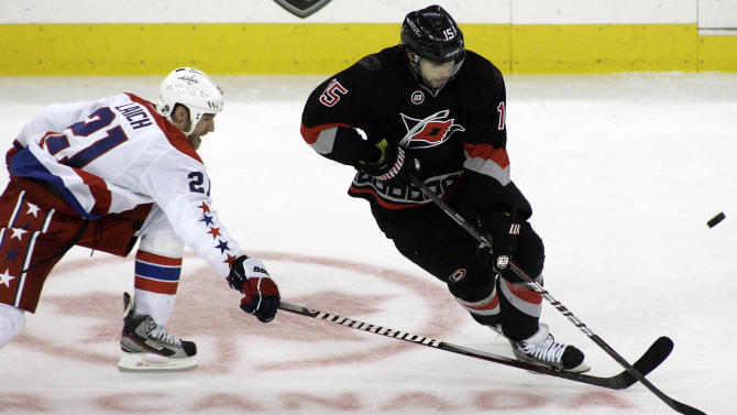 Carolina Hurricane's center Tuomo Ruutu (15) battles Washington Capital's center Brooks Laich (21) for the puck during the second period of an NHL hockey game in Raleigh, N.C., Friday, Jan. 20, 2012. (AP Photo/Jim R. Bounds)