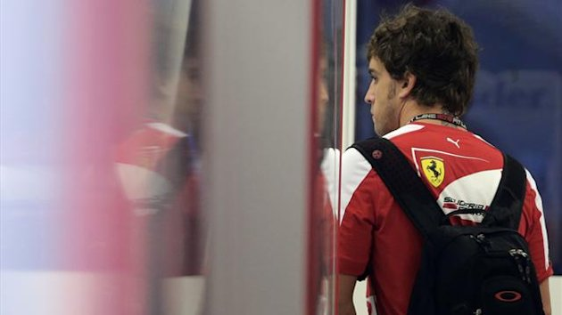 Ferrari Formula One driver Fernando Alonso of Spain walks into his garage after arriving at the paddock ahead of the Singapore F1 Grand Prix September 19, 2013. (Reuters)