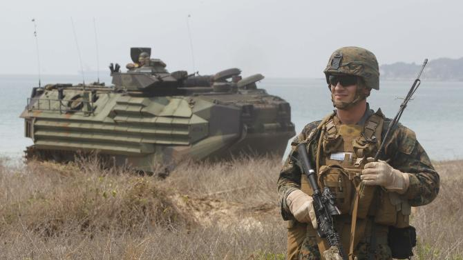 A U.S. Marine stands next to a amphibious assault vehicle (AAV) as he participates in an amphibious assault exercise in Chonburi province