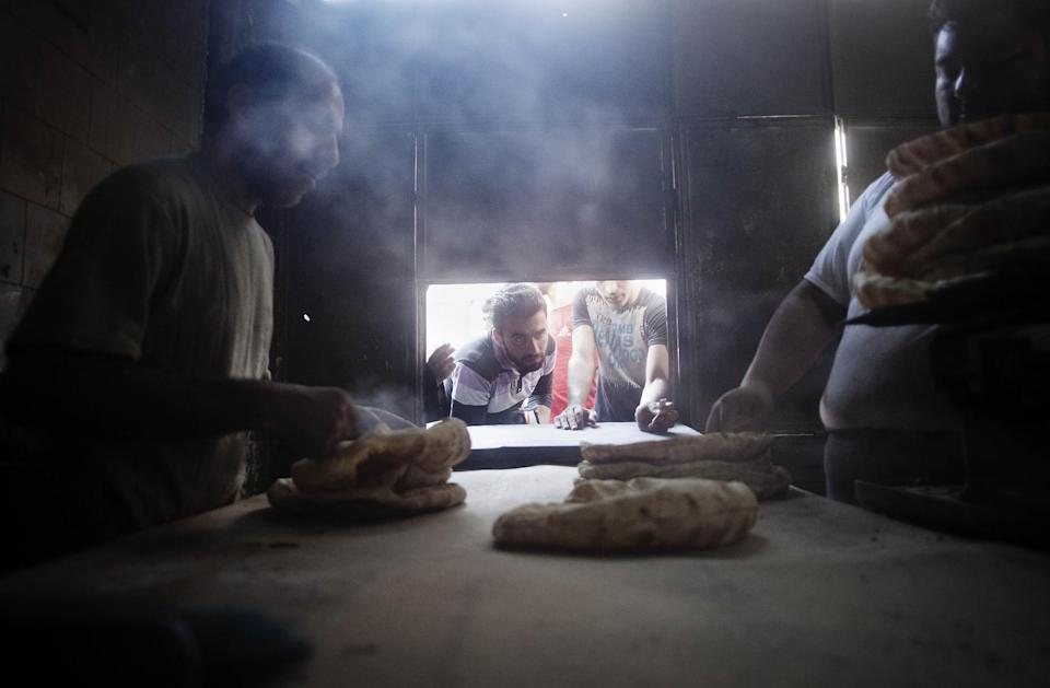 In this Saturday, Sept. 22, 2012 photo two Syrian men work at a bakery in Saif al Dawla neighborhood of Aleppo, Syria. (AP Photo/ Manu Brabo)