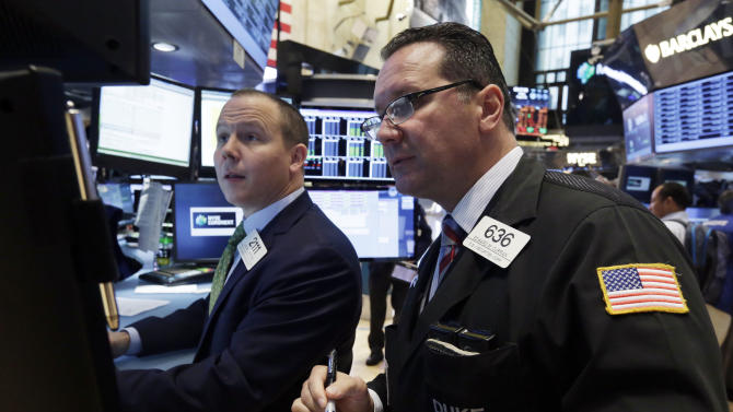 In this Friday, Aug. 16, 2013 photo, specialist Jason Notter, left, and trader Edward Curran work on the floor of the New York Stock Exchange. Stock futures are almost at a standstill, Monday, Aug. 19, 2013, as markets await any hint of changes in Fed thinking within the minutes from its July economic policy meeting later this week. (AP Photo/Richard Drew)