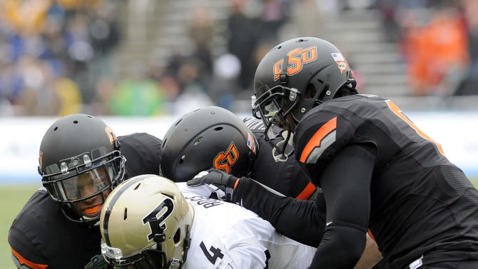 From left, Oklahoma State cornerback Kevin Peterson, linebacker Alex Elkins and safety Daytawion Lowe tackle Purdue wide receiver O.J. Ross (4) in the first half of the Heart of Dallas Bowl NCAA college football game, Tuesday, Jan. 1, 2013,in Dallas. (AP Photo/Matt Strasen)