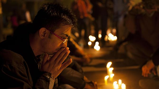 An Indian participates in a candle-lit vigil to mourn the death of a gang rape victim in New Delhi, India, Saturday, Dec. 29, 2012. Indian police charged six men with murder on Saturday, adding to accusations that they beat and gang-raped the woman on a New Delhi bus nearly two weeks ago in a case that shocked the country. The murder charges were laid after the woman died earlier Saturday in a Singapore hospital where she has been flown for treatment. (AP Photo/ Dar Yasin)