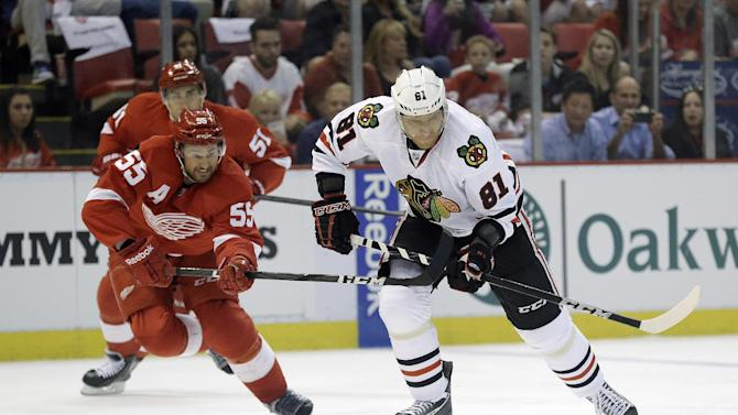 Detroit Red Wings defenseman Niklas Kronwall (55), of Sweden, tries to slow Chicago Blackhawks right wing Marian Hossa (81), of the Czech Republic, during the first period of an NHL hockey Stanley Cup playoffs Western Conference semifinal game in Detroit, Monday, May 20, 2013. (AP Photo/Paul Sancya)