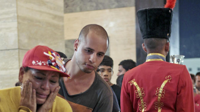 In this photo provided by Miraflores Presidential Press Office, mourners pay their respects as they file past the glass-topped casket containing the remains of Venezuela's late President Hugo Chavez lying in state at the military academy in Caracas, Thursday, March 7, 2013. Chavez died of a massive heart attack Tuuesday after great suffering and inaudibly mouthed his desire to live, the head of Venezuela's presidential guard said late Wednesday. (AP Photo/Miraflores Presidential Press Office)