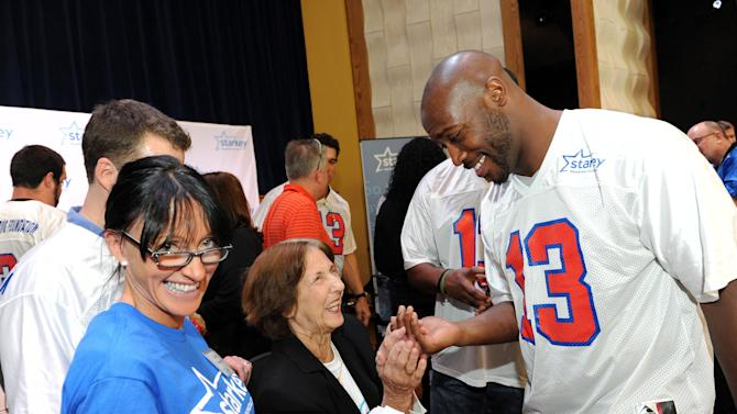 IMAGE DISTRIBUTED FOR STARKEY HEARING FOUNDATION - Will Witherspoon of the Tennessee Titans, right, celebrates with Anita Erickson who received a new hearing aid from the Starkey Hearing Foundation on Saturday, Feb. 2, 2013 in New Orleans. (Photo by Cheryl Gerber/Invision for Starkey Hearing Foundation/AP Images)
