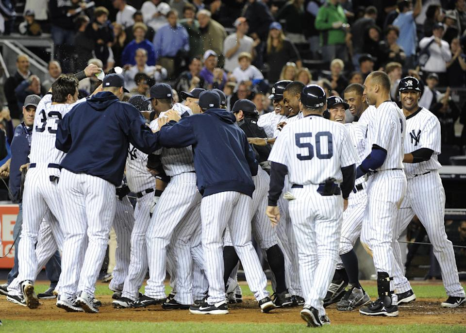 New York Yankees surround Russell Martin after he hit a solo home run off Oakland Athletics relief pitcher Sean Doolittle to give the Yankees a 2-1 win in the 10th inning of a baseball game Friday, Sept. 21, 2012, at Yankee Stadium in New York. (AP Photo/Kathy Kmonicek)