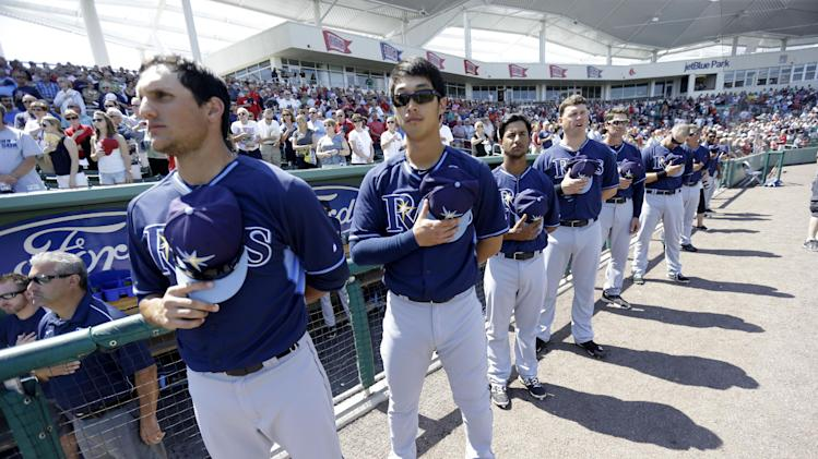 Tampa Bay Rays stand at attention with his team for the National Anthem before an exhibition baseball game against the Boston Red Sox in Fort Myers, Fla., Monday, March 10, 2014. (AP Photo/Gerald Herbert)