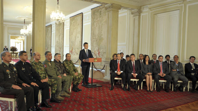 In this photo released by Colombia's Presidential Office, shows President Juan Manuel Santos, center, announcing the signing of a preliminary agreement to launch peace talks with the Revolutionary Armed Forces of Colombia, or FARC, during a nationally televised speech from the presidential palace in Bogota, Tuesday, Sept. 4, 2011. Santos said the talks would begin in early October in Oslo, Norway, and would continue in Havana, Cuba. Sitting at right are cabinet ministers and at left chiefs of the armed forces. (AP Photo/Javier Casella, Colombia's Presidential Office)