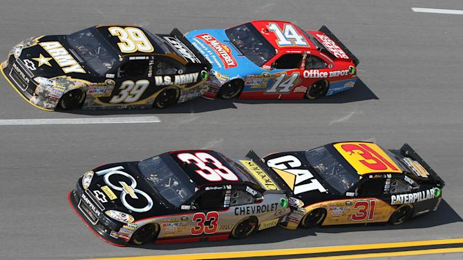 Clint Bowyer (33) and Jeff Burton (31) work low and Ryan Newman (39) and Tony Stewart (14) work high during the NASCAR Sprint Cup Series auto race at Talladega Superspeedway Sunday, Oct. 23, 2011, in Talladega, Ala. Bowyer won the race.  (AP Photo/Butch Dill)