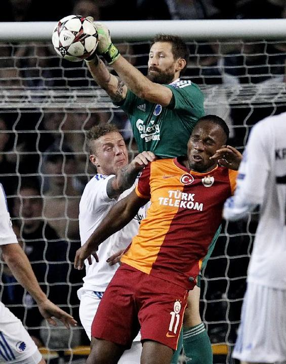 Galatasaray's Didier Drogba, right, and FC Copenhagen's goalkeeper Johan Wiland of Sweden, center, compete for the ball during their Champions League Group B soccer match at Parken Stadium, Copenhagen