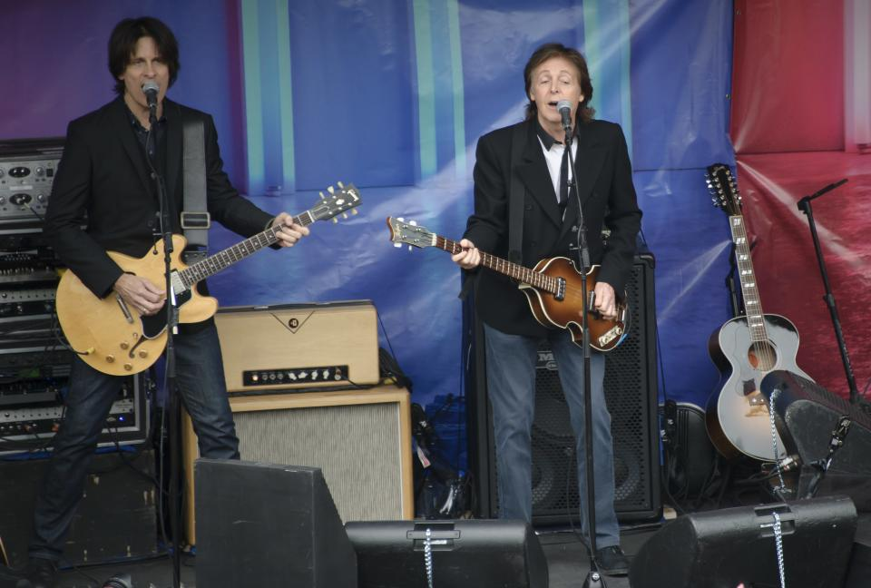 British singer Sir Paul McCartney, right, performs, in Covent Garden, London, Friday, Oct. 18, 2013. The surprise gig lasted for 20 minutes during lunchtime following a similar appearance in New York last Friday. (Photo by Jonathan Short/Invision/AP)